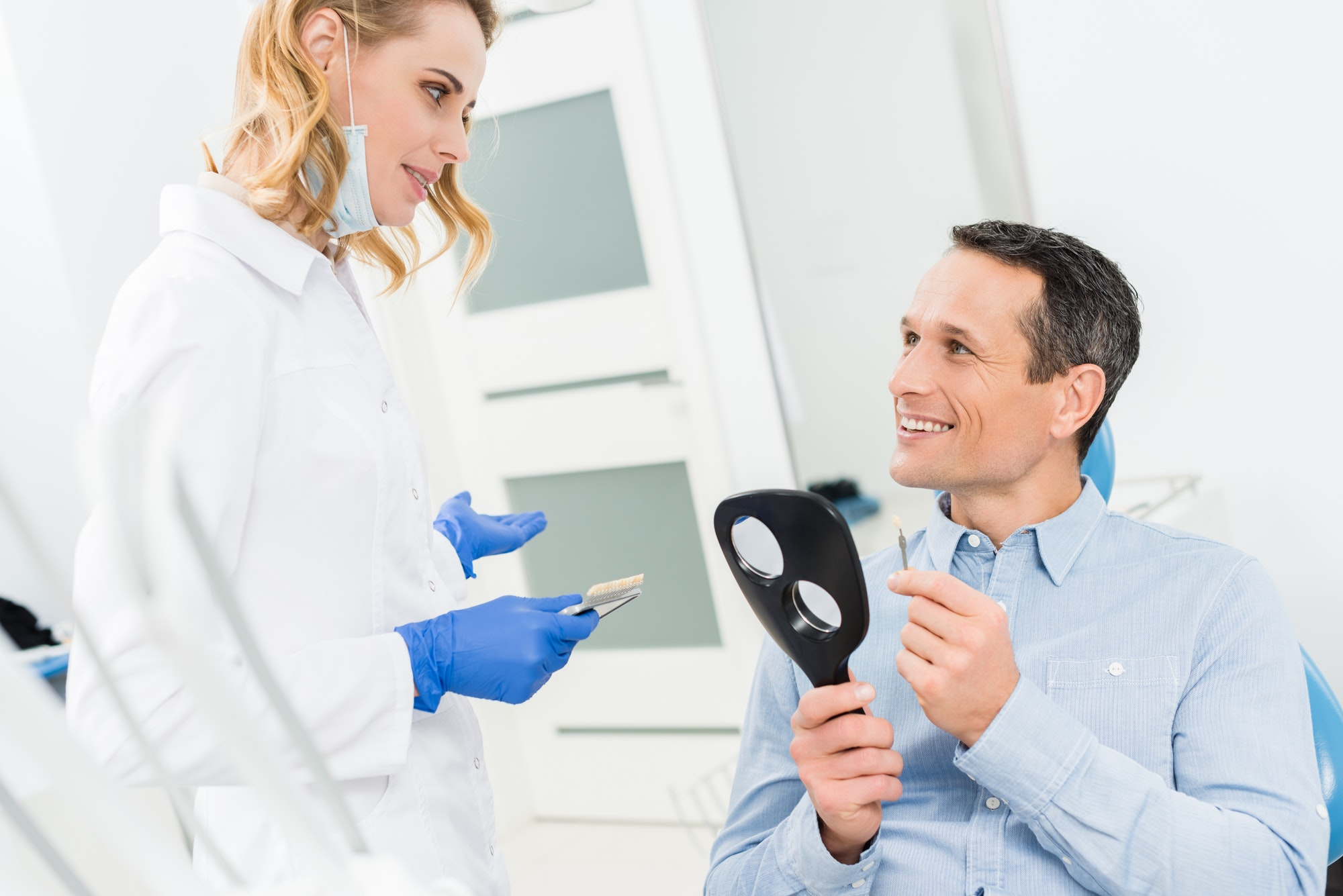 Male patient choosing tooth implant in modern dental clinic
